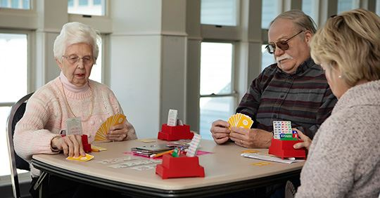Seniors seated at a table playing a card game